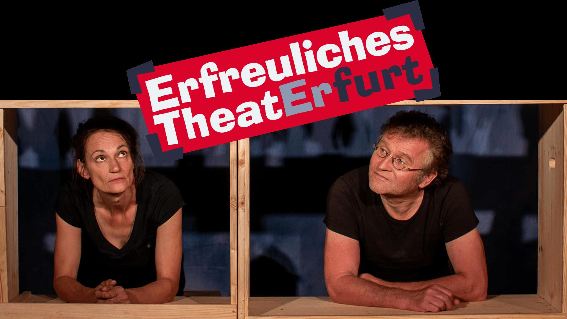 """Katrin Heinke und Ronald Mernitz schauen durch hölzerne Rahmen auf das Logo des """"Erfreuliches Theater Erfurt"""""""